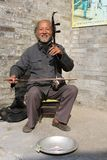 A man is playing the traditional musical instrument which is called Erhu or Nanhu and sounds like a violin Stock Images
