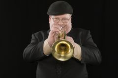 Man Playing Trumpet. Portrait of man playing trumpet isolated over black background Royalty Free Stock Photography