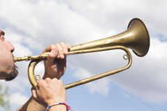 Man playing trumpet. On sky background Stock Photo
