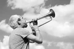 Man playing trumpet. On sky background Stock Photos