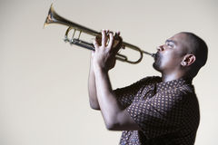 Man Playing Trumpet. Side view of an African American man playing trumpet against gray background Royalty Free Stock Photos