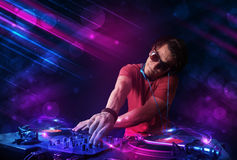 Man playing on turntables with color light effects Stock Photos