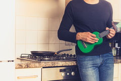Man is playing ukulele in the kitchen