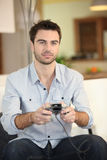 Man playing a video game. At home Royalty Free Stock Photos