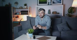 Man playing video game and chewing popcorn enjoying leisure at night. Man is playing video game using joystick and chewing popcorn enjoying leisure time alone at stock video
