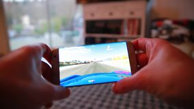 Man Playing A Video Game On His Smartphone At Home. Paris, France, January 25, 2017: Man Playing Real Racing 3 EA Games Video Game On His Modern Smartphone stock video footage