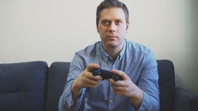 Man playing video game. Man playing racing video game on TV. Gamepad controller in hands stock video footage