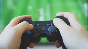 Man playing video game. Man playing soccer video game on TV. Gamepad controller in hands stock video footage