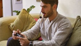 Man playing video game and talking with online players Royalty Free Stock Image