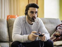 Man playing video game and talking with online players. Young handsome man playing video game and talking with online players through headset, while sitting on Royalty Free Stock Photos