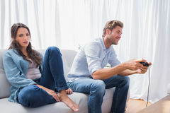 Man playing video games next to his annoyed partner Stock Photos
