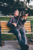 Man Playing Violin on Bench at Park Royalty Free Stock Image