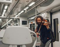 Man Playing Violin Inside Train royalty free stock photo