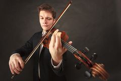Man playing violin showing emotions and expressions. Music passion, hobby concept. Man playing violin showing happy emotions and face expressions. Studio shot on Royalty Free Stock Image
