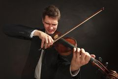 Man playing violin showing emotions and expressions. Music passion, hobby concept. Man playing violin showing hard emotions and face expressions. Studio shot on Royalty Free Stock Photos