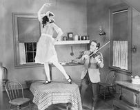 Man playing violin for woman dancing on table Royalty Free Stock Images
