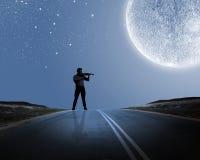 Man playing violin. Young man playing violin at night under moon light Stock Images