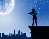 Man playing violin. Young man playing violin at night under moon light Stock Photography
