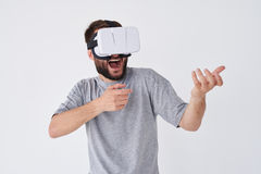 Man playing a virtual reality simulation with glasses making gestures with hands as if using a weapon. Close-up shot of bearded man playing a virtual reality stock image