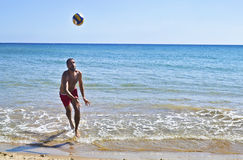 Man playing voleyball on beach royalty free stock photography
