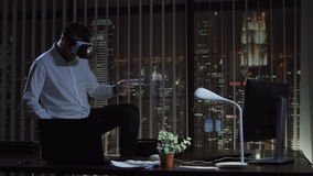 Man playing VR in office. Man in virtual reality headset playing in office at night. The office manager plays the guitar and then the drums stock video