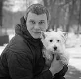 Man playing with a white dog winter snow Stock Image