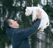 Man playing with a white dog winter snow Royalty Free Stock Photo