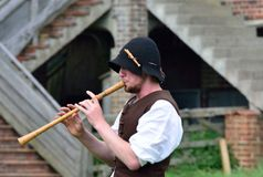 Man playing wooden medieval flute in reenactment Stock Images