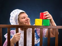 Man in playpen playing. Man weared as baby playing in playpen Royalty Free Stock Images