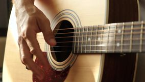 A man plays an acoustic guitar. Music and Hobbies. Close up stock video footage