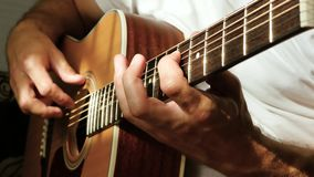 A man plays an acoustic guitar. The rays of the sun pass through the strings. Music and Hobbies. Close up stock video