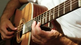 A man plays an acoustic guitar. The sun`s rays Shine through the strings of a guitar. Music and hobbies. 4K stock footage