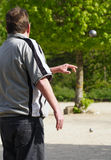 Man throwing ball in petanque. Man throwing ball onto pitch in game of petanque stock images