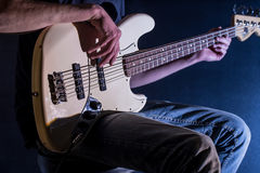 The man plays bass guitar on a black background, the music concept, beautiful lighting on the stage. Closeup Royalty Free Stock Image