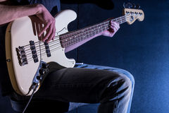The man plays bass guitar on a black background, the music concept, beautiful lighting on the stage. Closeup Stock Photos