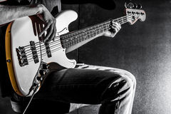 The man plays bass guitar on a black background, the music concept, beautiful lighting on the stage. Closeup Royalty Free Stock Images