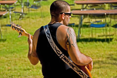 Man plays bass guitar outdoor Stock Photos
