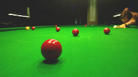 A man plays Billiards. Bright colorful balls to play snooker. Dim lights Stock Photo