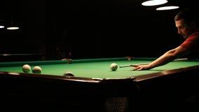 A man plays billiards. A man plays billiards in a dark room stock video