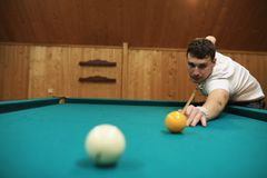 Man plays billiards. And takes aim before the turnr Royalty Free Stock Photography