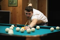 Man plays billiards. And takes aim before the turnr Royalty Free Stock Photos