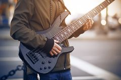 A man plays a black bass guitar on the street royalty free stock images