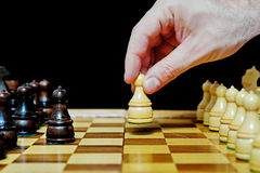 Man plays chess and makes first move. Closeup Royalty Free Stock Image
