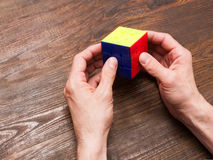 Man plays a cube of Rubik on wooden background royalty free stock image