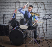 The man plays drums. The young man in a vest, a tie and with a small beard, plays drums Stock Photos