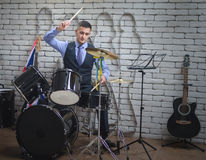 The man plays drums. The young man in a vest, a tie and with a small beard, plays drums Royalty Free Stock Photos
