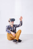 Man plays funny game. With expanded reality using glasses while sitting in white empty room stock photos