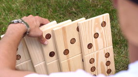 Man plays in a giant Domino on the grass in Park. stock video