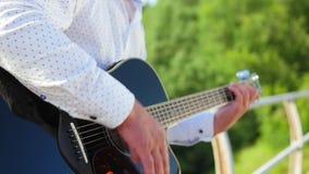 Man plays guitar. Guitarist is touching guitar strings. Close up shot. stock video footage