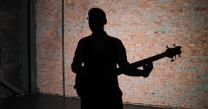 A man plays guitar while he is silhouetted from behind by a bright light. A silhouette of a guitar player. Man lead guitarist playing electrical guitar stock video footage